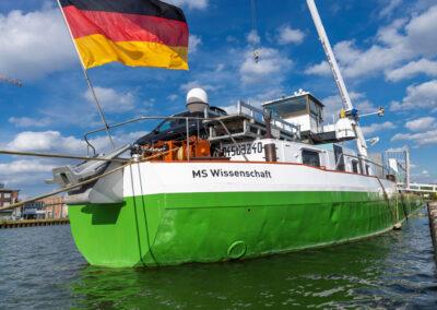Die MS Wissenschaft von schräg steuerbord achtern mit wehender Deutschlandfahne