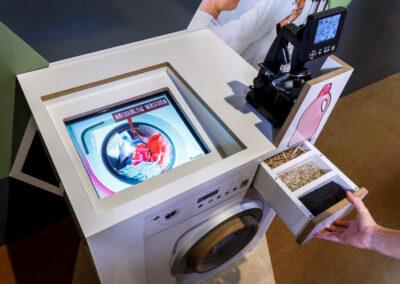"""Exponat """"Sauber dank Pilzen"""": Nachbau einer Waschmaschine mit Sporen und Pilzen im Waschmittelfach"""