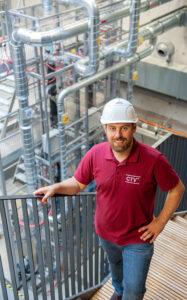 Prof. Dr.-Ing. Jakob Burger steht vor seiner neu errichteten Demonstrationsanlage am TUM Campus Straubing