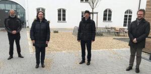 Vier Personen stehen im winterlichen Innenhof des Campus Straubing