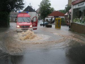 Hochwasser drückt einen Gullideckel hoch. Im Hintergrund ein Feuerwehrfahrzeug.